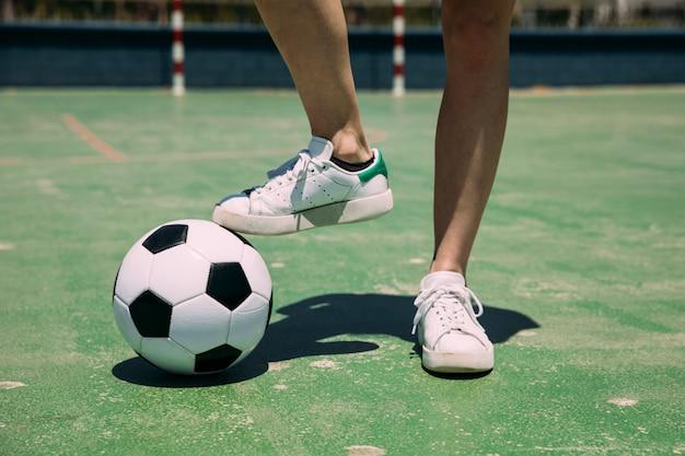 Giocatore con pallone da calcio con gamba in stadio Foto Gratuite