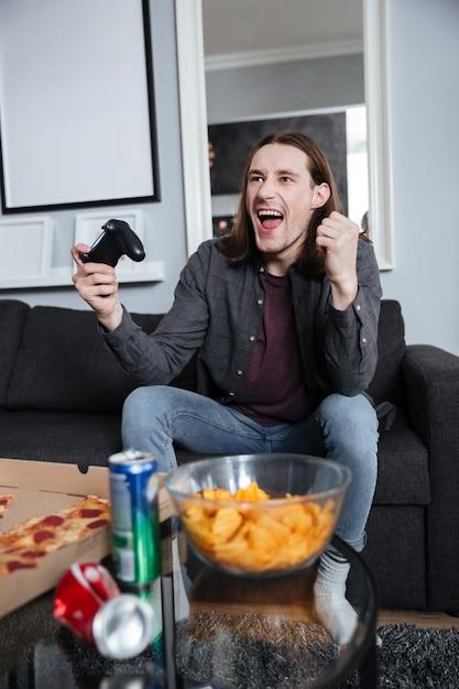 Giocatore dell'uomo felice che si siede a casa e gioca Foto Gratuite