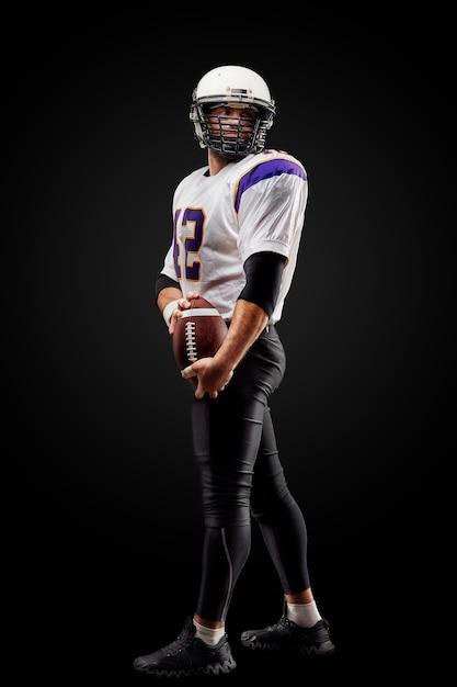 Giocatore dello sportivo di football americano sul nero. sport . Foto Premium