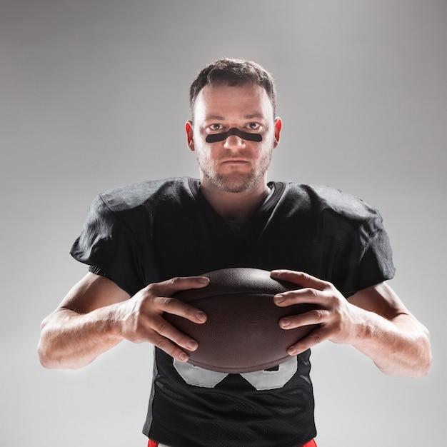 Giocatore di football americano che posa con la palla Foto Gratuite