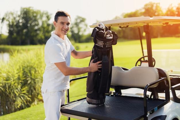 Giocatore di golf fiero vicino a buggy car hobby costoso. Foto Premium