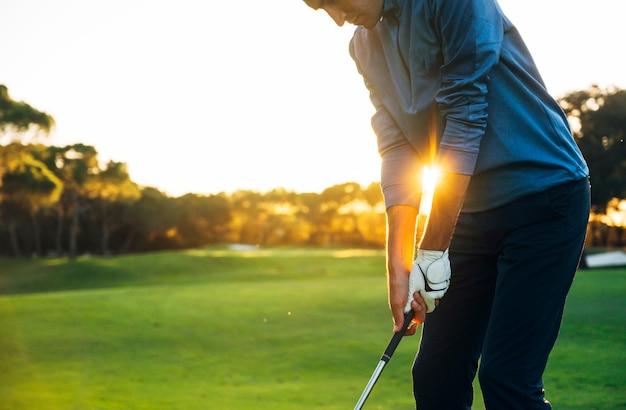 Giocatore di golf maschio che colloca sul tee fuori dalla palla da golf dalla scatola del t al bello tramonto Foto Premium