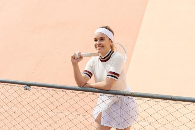 Giocatore di tennis femminile felice con la racchetta Foto Gratuite