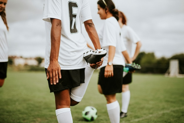 Giocatori della squadra di calcio femminile che si allungano pre gioco Foto Premium