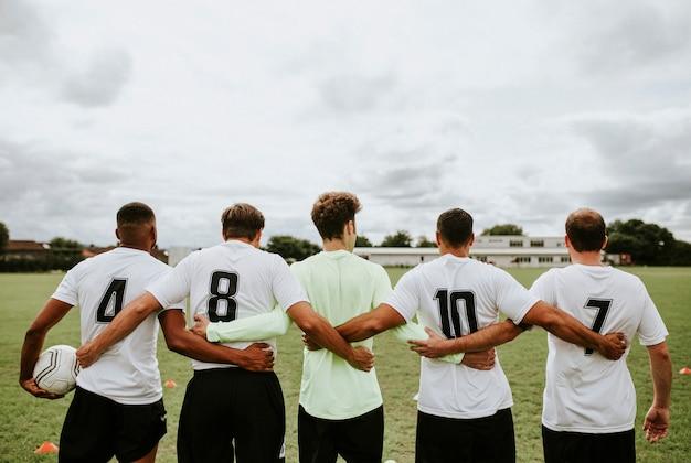 Giocatori di football che stanno insieme parallelamente Foto Premium