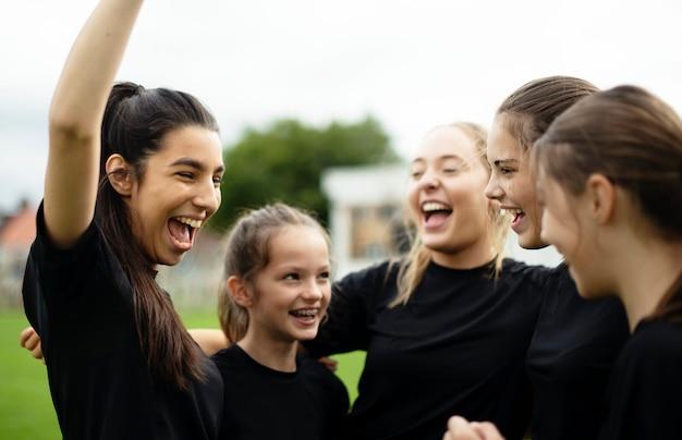 Giocatori di football femminile allegri che celebrano la loro vittoria Foto Premium