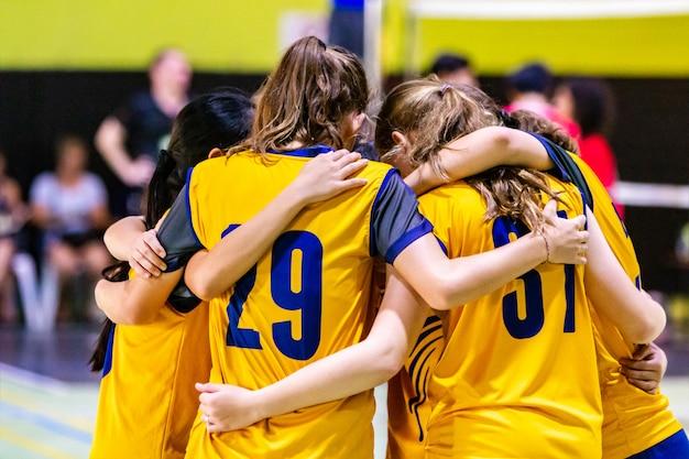 Giocatori di pallavolo femminile che si accalcano insieme prima di iniziare il gioco Foto Premium