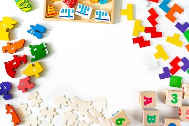 Giocattoli colorati per bambini su sfondo bianco. inquadra dallo sviluppo di blocchi di legno, automobili e puzzle. giocattoli naturali ed ecologici per bambini. vista dall'alto. disteso. copia spazio. Foto Premium