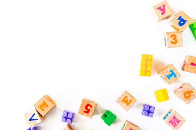 Giocattoli colorati per bambini su sfondo bianco. inquadra dallo sviluppo di blocchi di legno, automobili e puzzle. Foto Premium