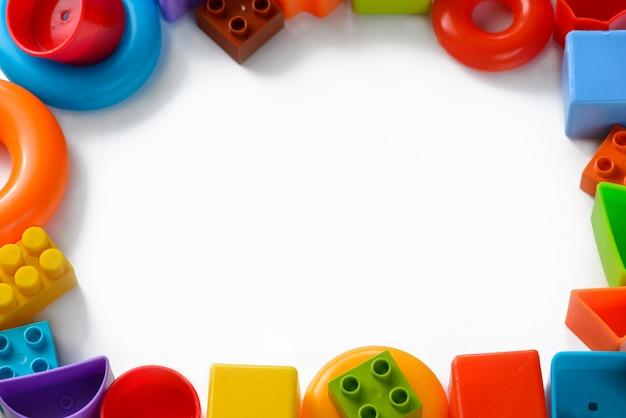 Giocattoli per bambini multicolori sotto forma di una cornice su uno sfondo bianco Foto Premium