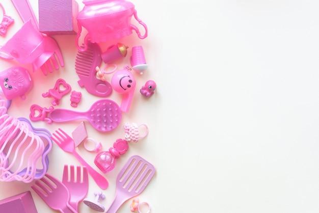 Giocattoli rosa baby su fondo bianco. vista dall'alto. bambino disteso. copyspace Foto Premium