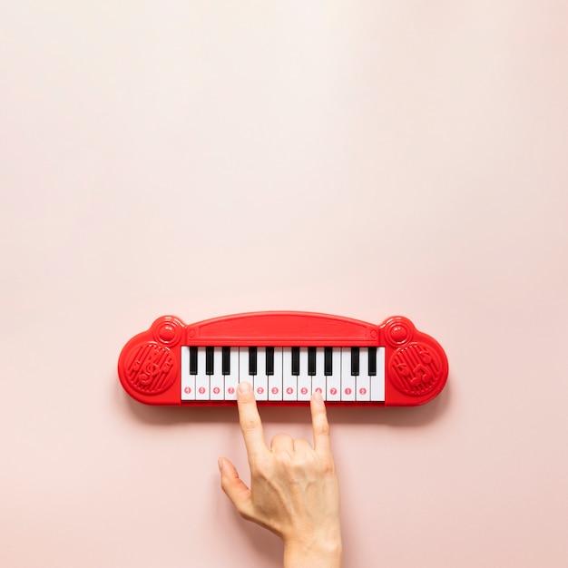 Giocattolo del piano e della mano su fondo rosa Foto Gratuite