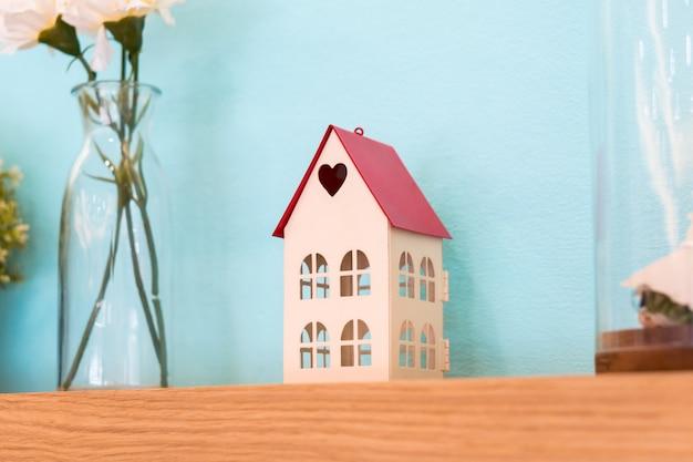 Giocattolo della casetta con forma di cuore sulla decorazione di scaffale in legno Foto Premium