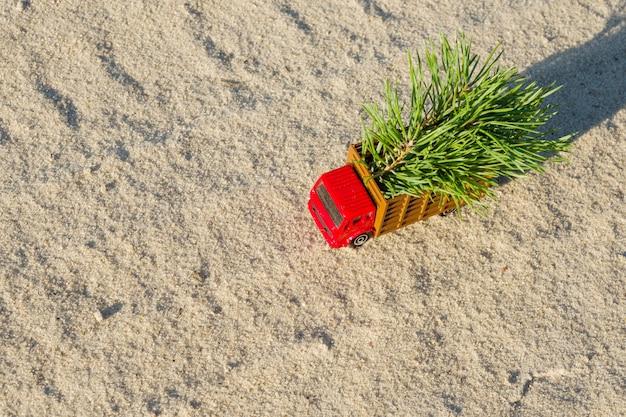 Giochi il camion con l'albero di natale sul sentiero forestale del paese Foto Premium