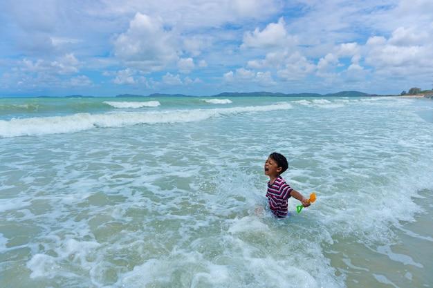 Gioco asiatico del bambino nel mare Foto Premium