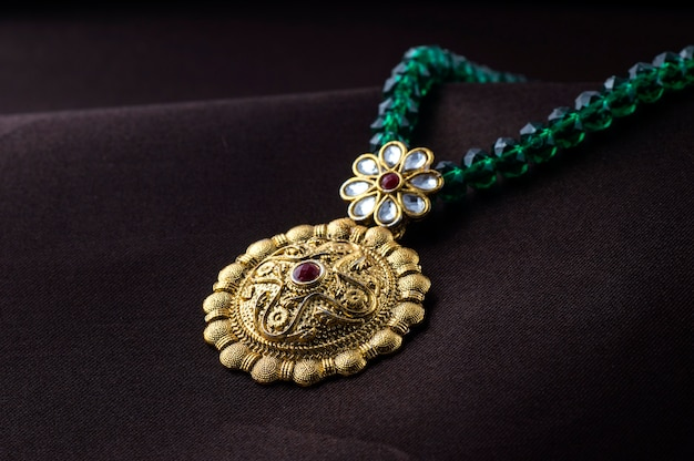 Gioielli tradizionali indiani, primi piani di pendenti su spazio scuro Foto Premium