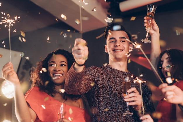 Gioiosa e felice. amici multirazziali festeggiano il nuovo anno e tengono in braccio luci e bicchieri di bengala Foto Premium