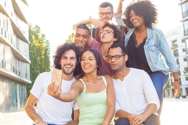 Gioiosa gente che correva insieme prendendo selfie di gruppo Foto Gratuite