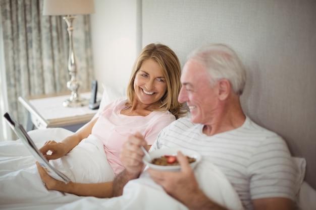 Giornale sorridente della lettura delle coppie mentre mangiando prima colazione Foto Premium