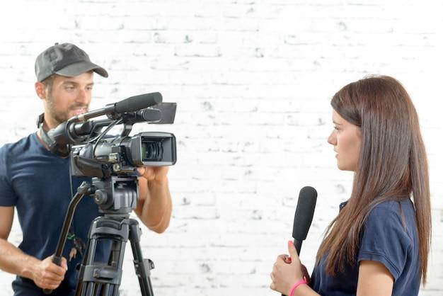 Giornalista di giovane donna con microfono e cameraman Foto Premium