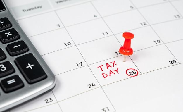 Giornata fiscale scritta su un calendario con una puntina rossa. Foto Premium