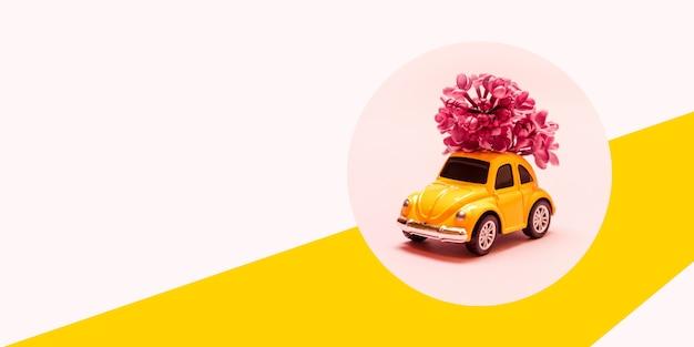 Giornata internazionale della donna felice. giochi l'automobile gialla con il ramo del fiore lilla su un fondo rosa con il posto per testo. Foto Premium