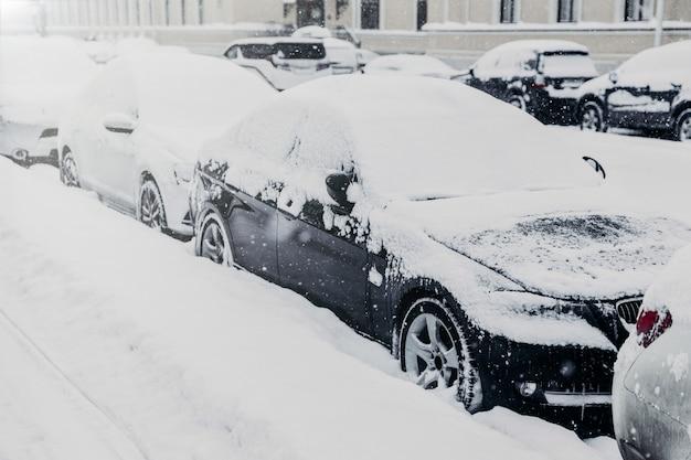 Giornata invernale nei dintorni urbani. le auto sono sul parcheggio, coperte di neve bianca dopo forti nevicate Foto Premium