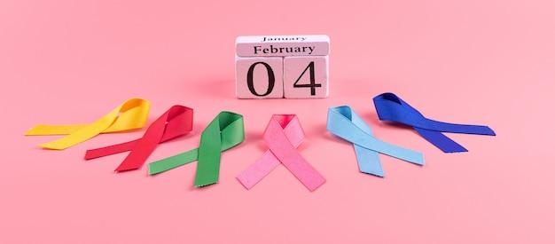 Giornata mondiale del cancro (4 febbraio). nastri colorati di consapevolezza; colore blu, rosso, verde, rosa e giallo su legno per sostenere le persone che vivono e le malattie. concetto di sanità e medicina Foto Premium