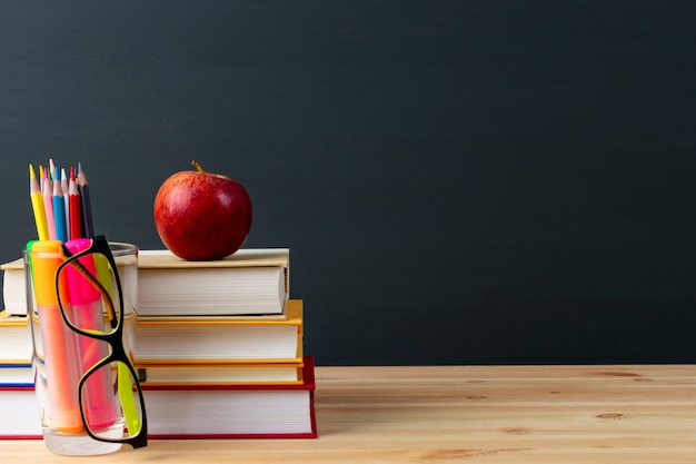 Giornata mondiale dell'insegnante, mela e libri con le matite e gli occhiali sul tavolo in aula. Foto Premium