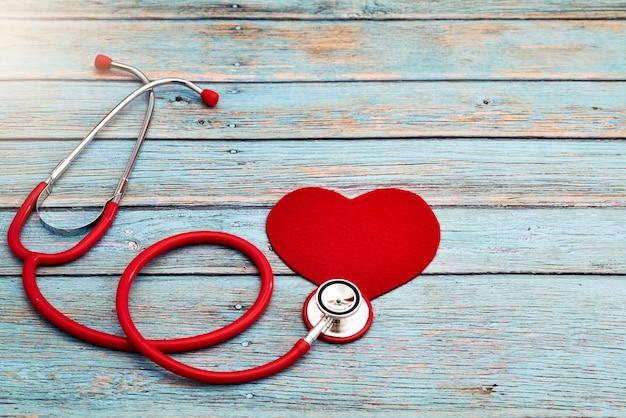 Giornata mondiale della salute, assistenza sanitaria e concetto medico, stetoscopio rosso e cuore rosso su fondo di legno blu Foto Premium
