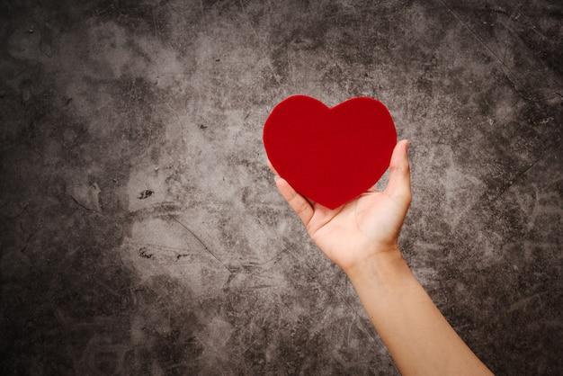 Giornata mondiale della salute, la mano delle donne tiene il cuore rosso su sfondo nero grunge Foto Premium