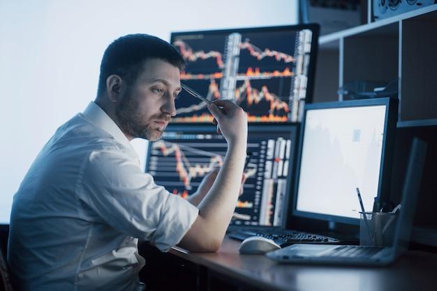Giornata stressante in ufficio. giovane uomo d'affari che si tiene per mano sul suo fronte mentre sedendosi allo scrittorio in ufficio creativo. grafico di borsa forex trading finanza Foto Premium