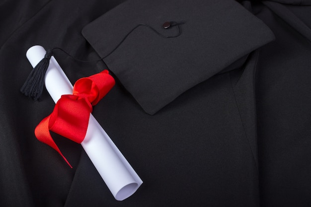 Giorno della laurea. un abito, cappello di laurea e diploma e pronto per il giorno della laurea Foto Premium
