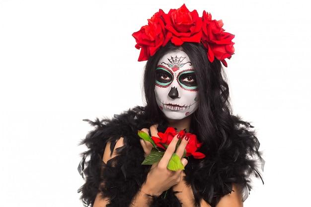 Giorno della morte. halloween. giovane donna nel giorno dei morti teschio maschera viso arte e rosa. isolato su bianco avvicinamento. Foto Premium