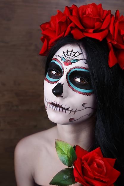 Giorno della morte. halloween. giovane donna nel giorno dei morti teschio maschera viso arte e rosa. sfondo scuro Foto Premium