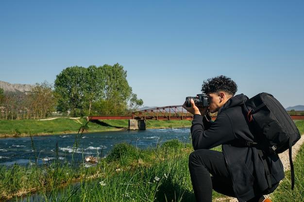 Giovane accovacciantesi che cattura maschera del fiume scorrente Foto Gratuite