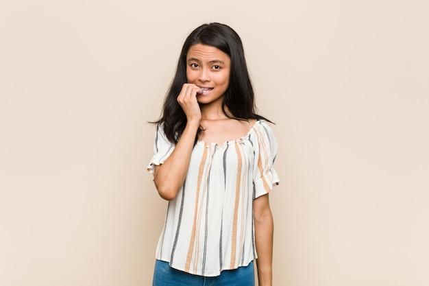 Giovane adolescente cinese carino giovane donna bionda che indossa un cappotto contro uno sfondo rosa unghie mordaci, nervoso e molto ansioso. Foto Premium