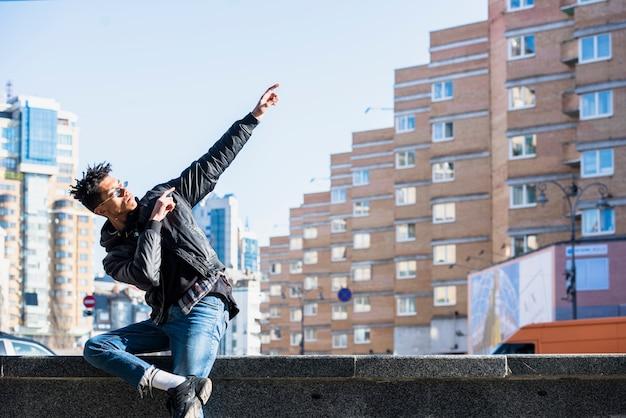 Giovane africano che si siede sulla parete che gesturing davanti alle costruzioni nella città Foto Gratuite