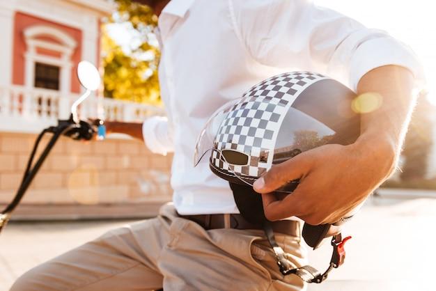 Giovane africano seduto su una moto moderna e tenendo casco da motociclista all'aperto Foto Gratuite