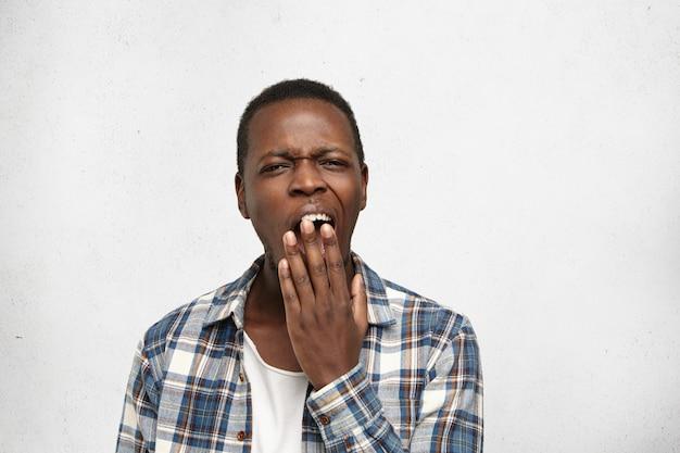 Giovane afroamericano stanco o annoiato che copre la bocca mentre sbadiglia, sentendosi esausto dopo una dura giornata di lavoro. studente maschio nero che ha sguardo noioso assonnato durante la lezione di storia all'università Foto Gratuite