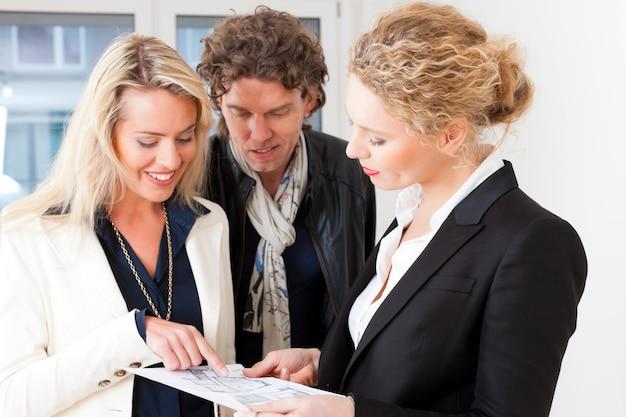 Giovane agente immobiliare che spiega piano terra per coppia Foto Premium