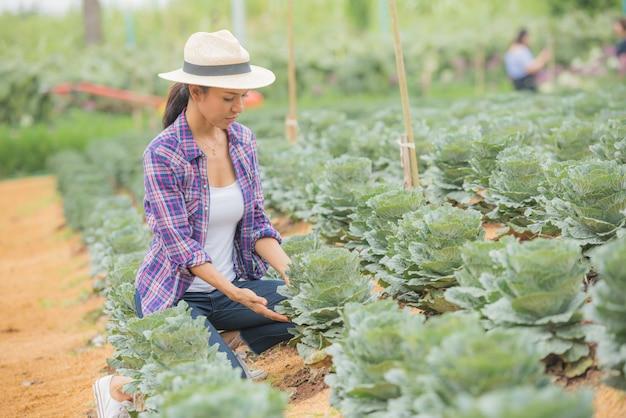 Giovane agricoltore che lavora nel campo e controlla le for Piante decorative