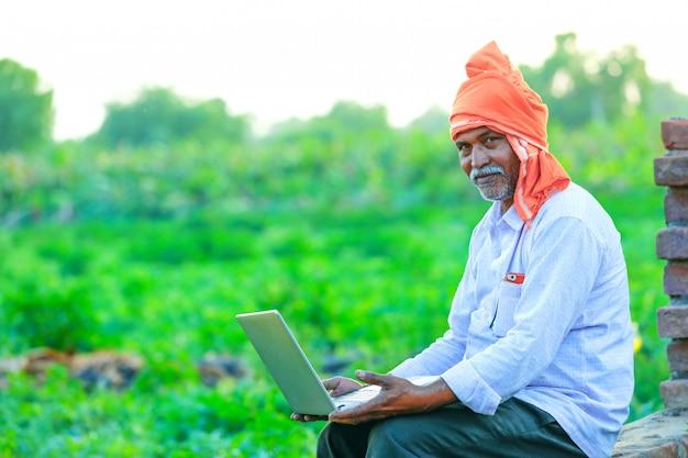 Giovane agricoltore indiano con il portatile al campo Foto Premium