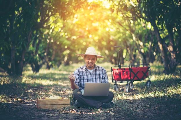 Giovane agricoltore intelligente che lavora con la compressa nel frutteto del mango, concetto agricolo di bisiness Foto Premium