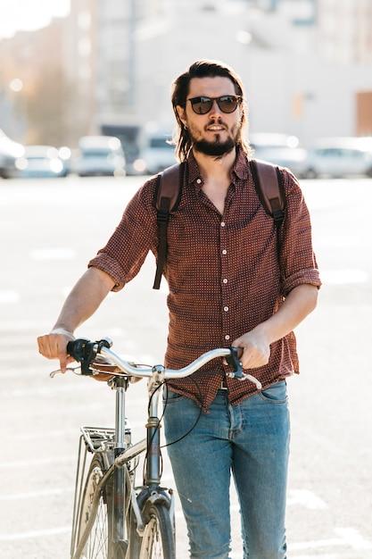 Giovane alla moda che cammina con la bicicletta sulla strada Foto Gratuite