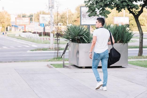 Giovane alla moda che cammina sulla strada Foto Gratuite