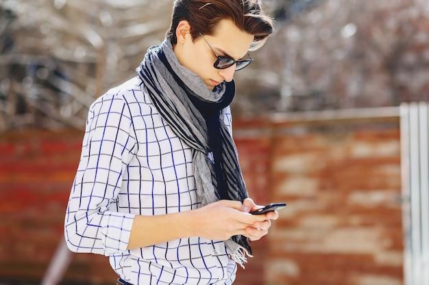 Giovane alla moda in occhiali da sole con il telefono sulla strada Foto Premium