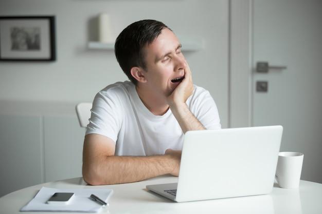 Giovane annoiato, sbadiglio, seduto alla scrivania bianca vicino al computer portatile Foto Gratuite