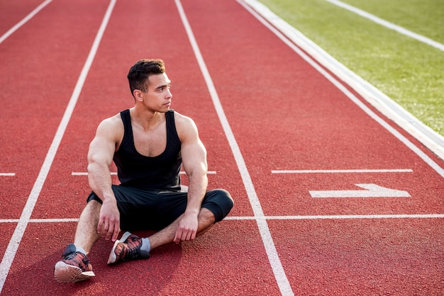 Giovane atleta maschio di forma fisica che si rilassa sulla pista di corsa rossa nello stadio Foto Gratuite