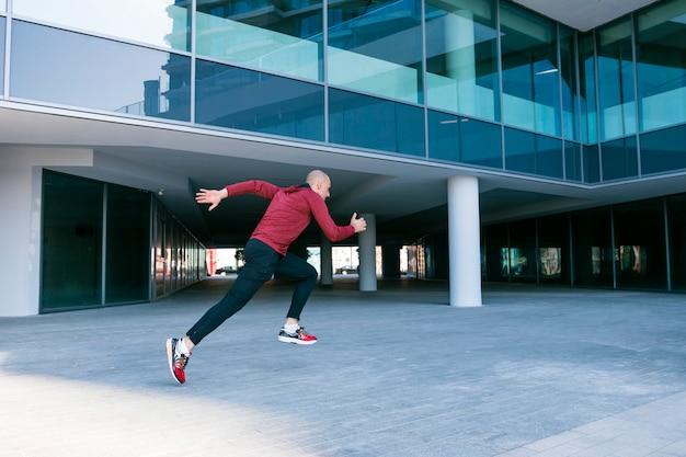 Giovane atleta maschio in buona salute allegro che corre vicino all'edificio corporativo Foto Gratuite